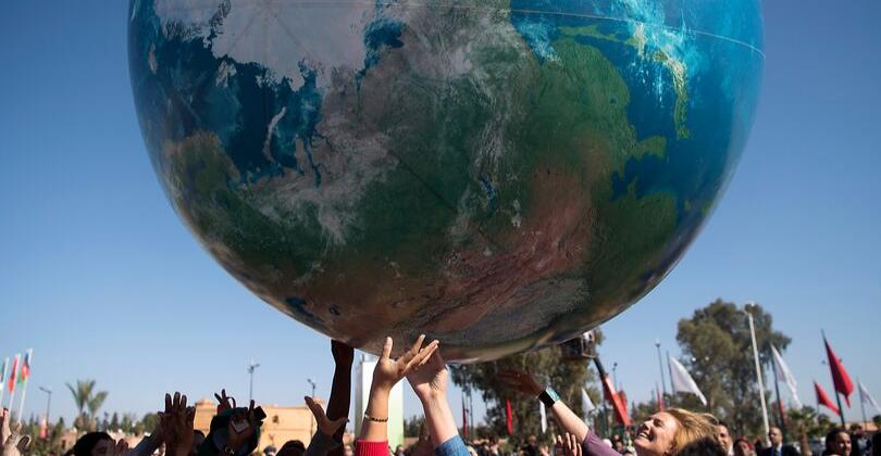Imagem de pessoas segurando uma réplica do planeta terra