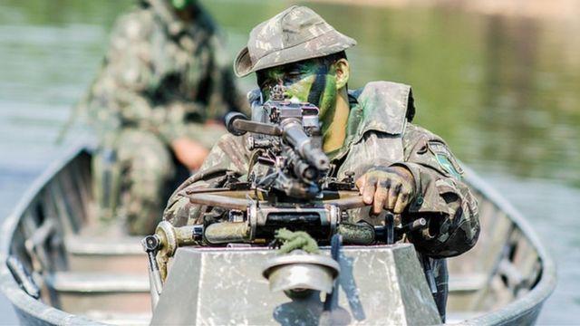 Imagem de soldado em barco na amazônia
